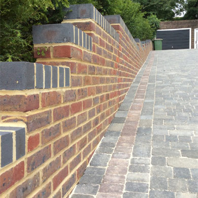 Image of new wall with two-tone brickwork and driveway