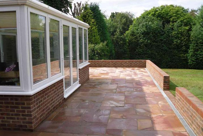 Photo of new patio in sandstone and low brick wall